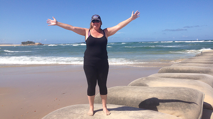 A photograph of a light skinned woman standing on a beach. The woman is wearing black yoga pants, a black tank top, a dark-colored baseball cap, and sunglasses. Her arms are outstretched, and she is smiling at the camera. The sky in the background is sunny and clear.